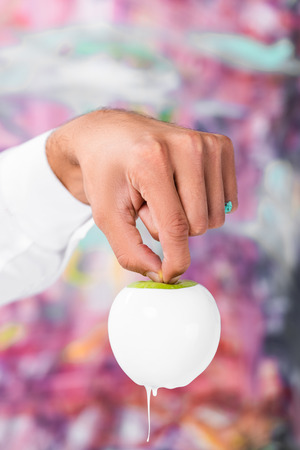 Close up of male hand holding white painted apple