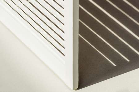 Close up of wooden white room divider against daylight with shadow