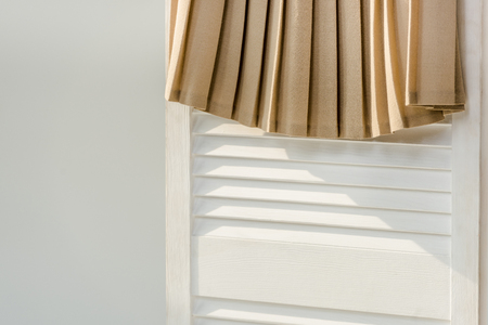 Close up of beige pleated skirt hanging on white room divider isolated on grey