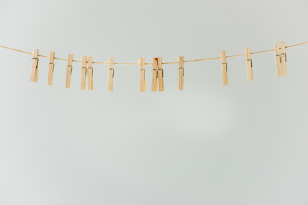 Close up of raw of wooden clothespins hanging on clothesline isolated on grey