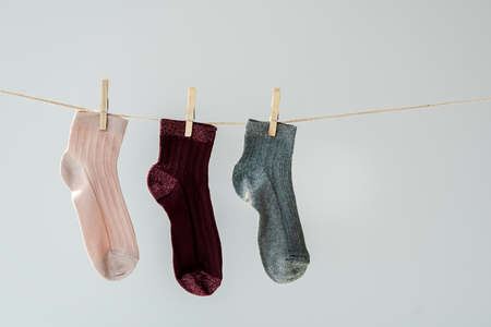 Close up of multicolored shiny socks hanging on clothesline isolated on grey