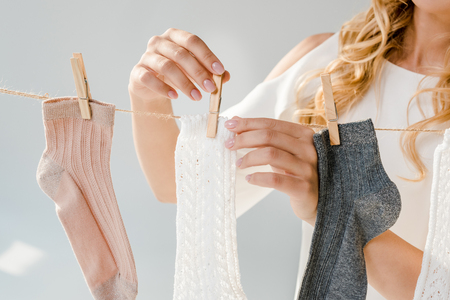Close up of woman putting socks on clothesline with clothespins