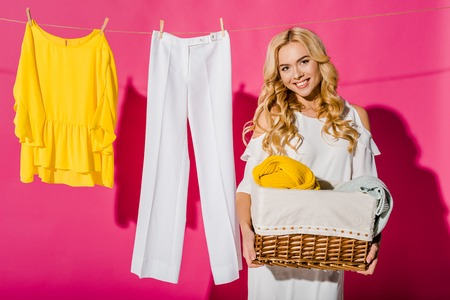 Close up of beautiful woman holding wicker basket with clothes hanging on clothesline