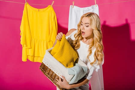 Close up of emotional woman getting out clothes from wicker basket Stock Photo