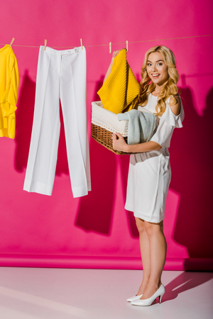 Beautiful smiling woman getting out clothes from wicker basket Stock Photo