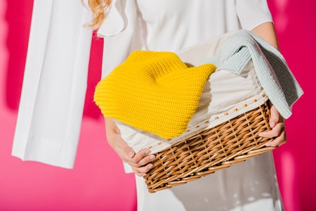 Close up of female hands holding wicker basket with clothes Banco de Imagens