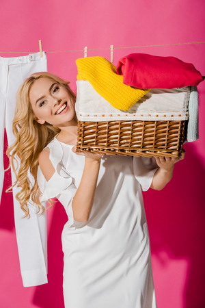 Close up of happy woman holding wicker basket with clothes