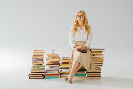 Beautiful adult woman sitting on pile of retro books