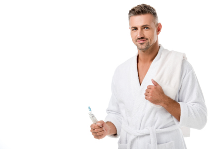 Happy adult man in bathrobe with towel over shoulder holding toothpaste and toothbrush isolated on white
