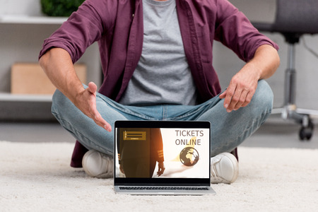 Cropped view of man pointing at laptop with tickets online illustration