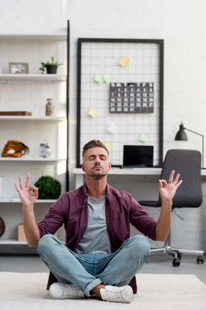 Man sitting on floor and practicing yoga at home office Banque d'images