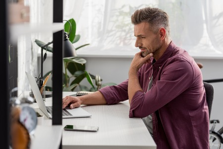Man sitting on chair and working on laptop at workplace