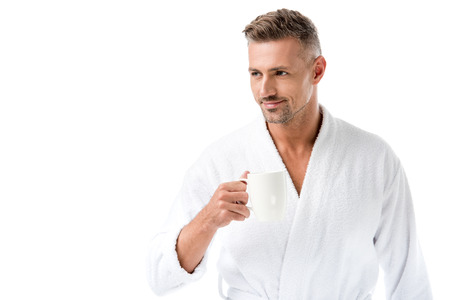 Cheerful man in bathrobe holding coffee cup isolated on white