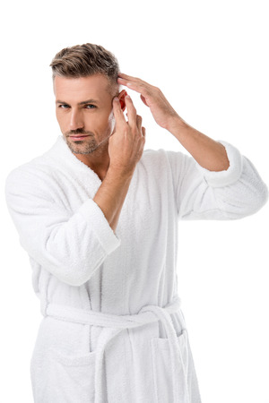 Adult man in bathrobe checking himself for hair loss isolated on white Foto de archivo - 112348732