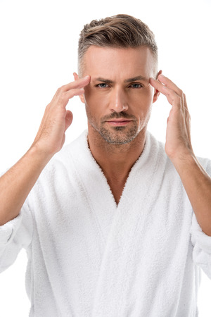 Upset man in bathrobe worrying about own appearance isolated on white
