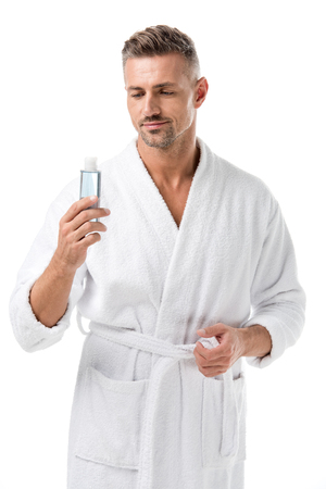 Man in bathrobe holding shaving lotion isolated on white