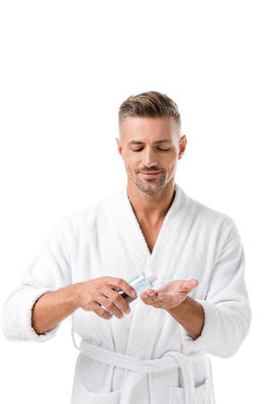 Joyful man in bathrobe using shaving lotion isolated on white