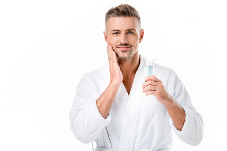 Portrait of cheerful man in bathrobe using shaving lotion isolated on white