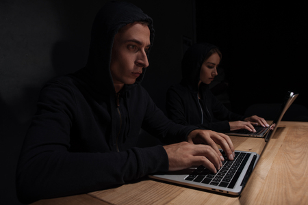 Hackers in black hoodies using laptops at wooden tabletop, cyber security concept