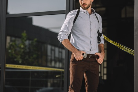 Male detective standing with arms akimbo Stock Photo - 112309477