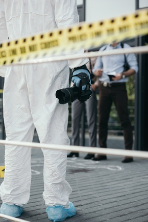 Cropped view of criminologist in protective suit and latex gloves with camera at crime scene