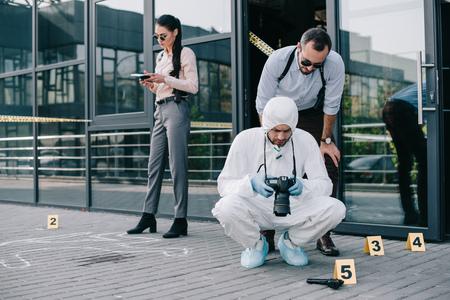 Detective masculino viendo fotos de la escena del crimen con criminólogo masculino mientras detective femenino tomando notas Foto de archivo