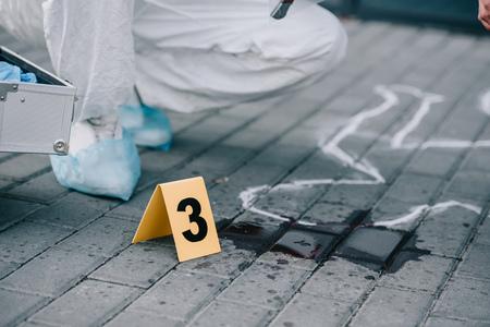 Teilansicht eines Kriminologen, der neben nummerierten Beweisen sitzt Standard-Bild