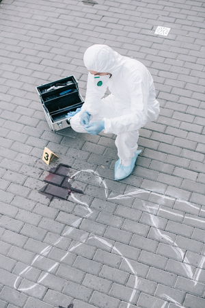 Male criminologist in protective suit and latex gloves looking at chalk line with blood spot at crime scene