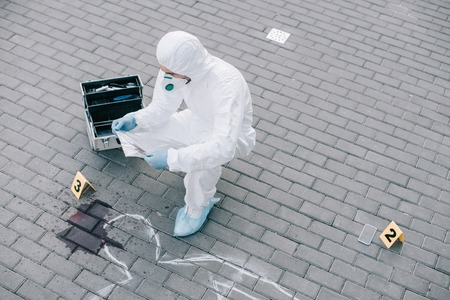 Male criminologist in protective suit and latex gloves explore evidence at the crime scene Archivio Fotografico - 112348822