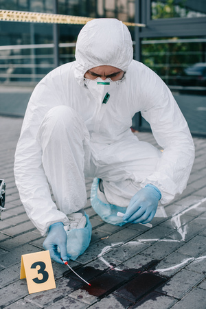 Male criminologist in protective suit  taking a blood sample 版權商用圖片