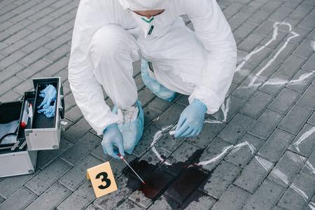Männlicher Kriminologe in Schutzanzug und Latexhandschuhen, der eine Blutprobe am Tatort nimmt