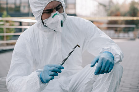 Male criminologist in protective suit and latex gloves looking at evidence into flask at crime scene Stock Photo - 112317977