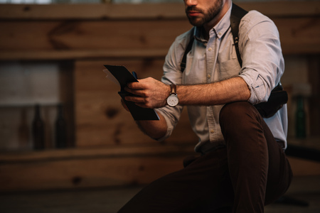 Cropped view of male detective making notes