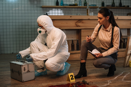 Forensic investigator and focused female detective taking notes and examining crime scene together Reklamní fotografie
