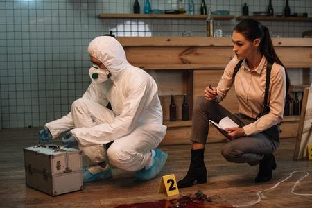 Investigadora forense y detective femenina enfocada tomando notas y examinando la escena del crimen juntas
