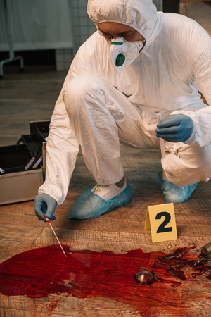 Cropped view of forensic investigator in latex gloves taking blood samples at crime scene 版權商用圖片