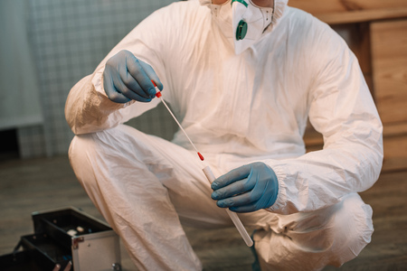 Cropped view of forensic investigator in latex gloves taking blood samples at crime scene Stock Photo