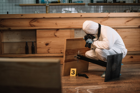Forensic investigator documenting evidence with camera at crime scene 版權商用圖片