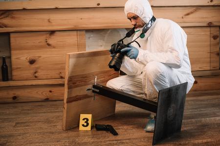 Investigador forense que documenta evidencia con cámara en la escena del crimen Foto de archivo