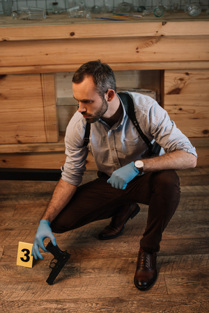 Focused male detective collecting evidence gun at crime scene Stock Photo - 112348849