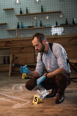 Concentrated male detective collecting evidence at crime scene Stock Photo