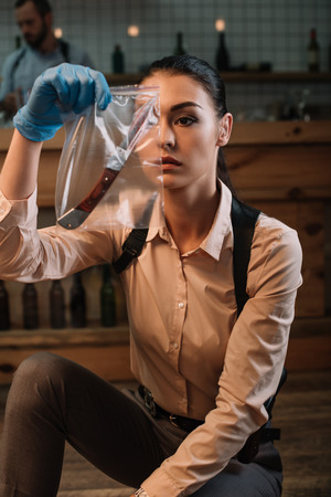 Focused female detective looking at evidence at crime scene Stock Photo