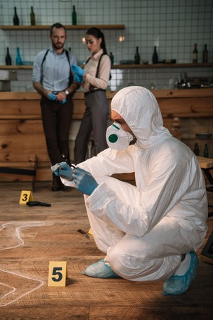 Concentrated forensic investigator examining evidence with magnifying glass at crime scene with colleagues working behind