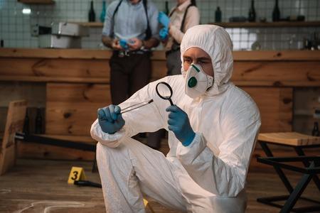 Investigador forense enfocado examinando evidencia con lupa en la escena del crimen con colegas que trabajan detrás Foto de archivo