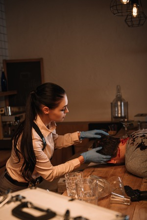 Side view of concentrated female detective examining dead body at crime scene Stock Photo - 112348933