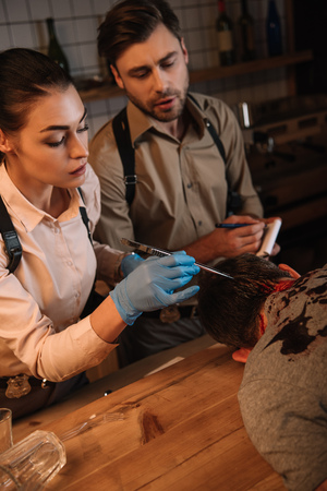 Cropped view of concentrated female and male detectives collecting evidence from dead body and investigating crime scene Stock Photo