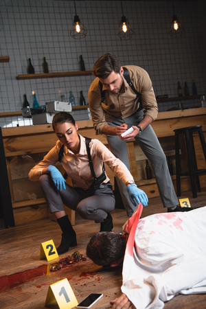 Focused female and male detectives investigating dead body at crime scene Banque d'images