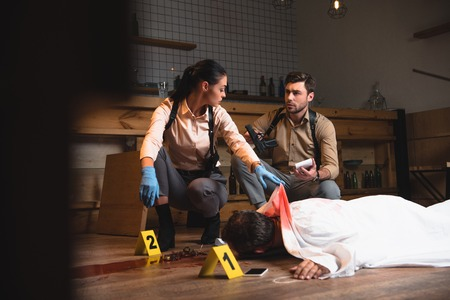 Serious female and male detectives investigating dead body at crime scene with evidence markers Banque d'images