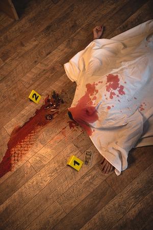 Draufsicht auf mit weißem Laken bedeckte Leiche am Tatort