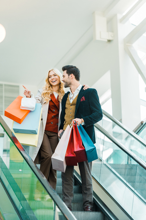 Beautiful couple with shopping bags standing on escalator